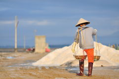 Vietnamese women are burdening hard to collect salt from the extract fields to the storage fields. NINH HOA, VIETNAM - MARCH 2, 2012: Vietnamese women are Stock Photos
