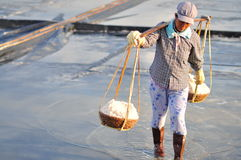 Vietnamese women are burdening hard to collect salt from the extract fields to the storage fields. NINH HOA, VIETNAM - MARCH 2, 2012: Vietnamese women are Stock Images