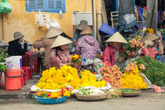 Vietnamese women in conical hat selling flowers at the street marke Royalty Free Stock Image