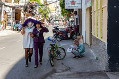 Vietnamese women hide from the sun on Bui Vien Street in Ho Chi Royalty Free Stock Images