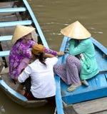 Vietnamese women on the Mekong River. Vietnamese women chatting on their boats on the Mekong River stock photo