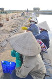 Vietnamese women salt workers are relaxing after working hard to collect salt from the extract fields to the storage fields Royalty Free Stock Photo