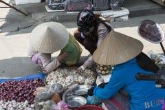 Vietnamese women on the street market. Hoian Vietnam. Vietnamese women choosing vegetables at the street market Hoian, Vietnam Stock Image