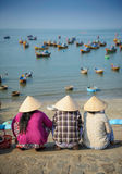 Vietnamese women waiting for fishing boats. To come to shore and unload their catch Royalty Free Stock Photos