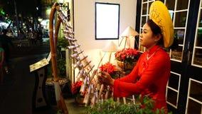 Vietnamese women wear Ao dai Playing T'Rung. HO CHI MINH-VIETNAM JAN 11: Unidentified Vietnamese women wear Ao dai Playing T'Rung on street in Ho Chi Minh, Viet stock video footage