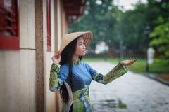 Vietnamese women wear Ao dai in the rain Royalty Free Stock Photo