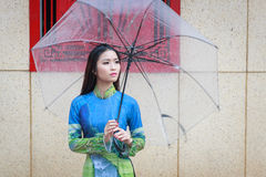 Vietnamese women wear Ao dai in the rain Stock Photo