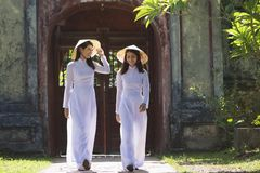 Vietnamese women wearing traditional suit walking in the temple royalty free stock images