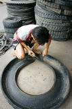 Vietnamese worker,  recycle tire, tyre Royalty Free Stock Photo