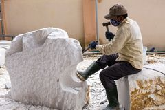 Vietnamese worker wearing breathing mask sculpting huge chunk of marble stock photos