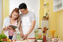 Follwing recipe. Vietnamese young couple following recipe on tablet computer Stock Image