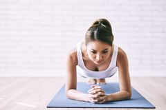 Plank exercise. Vietnamese young woman doing plank exercise to develop endurance royalty free stock image