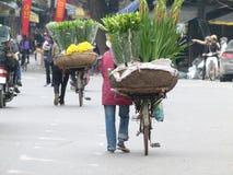 Vietnamesische Blumenschneider u. -trimmer, die Fahrräder drücken Lizenzfreies Stockfoto