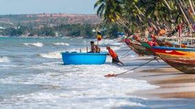Vietnamesische Fischer drücken ihren Fischen Coracle heraus zum Meer für ihre tägliche Aufgabe am Fischer Village, Mui Ne, Vietna Stockbilder