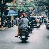 Vietnamesische Frau, die ein Motorrad reitet lizenzfreies stockbild
