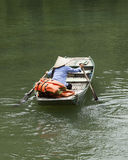 Vietnamesische Frau mit konischem Hut ihr Boot schaufelnd Lizenzfreie Stockfotos