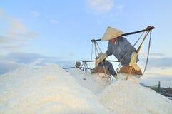 Vietnamesische Frauen belasten stark, um Salz von den Auszugfeldern zu den Speicherfeldern zu sammeln Stockfotos