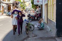 Vietnamesische Frauen verstecken sich von der Sonne auf Bui Vien Street in Ho Chi Lizenzfreie Stockbilder
