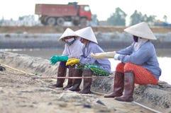 Vietnamesische Frauensalzarbeitskräfte sind entspannend, nachdem sie schwer, zum des Salzes von den Auszugfeldern zu den Speicher Lizenzfreies Stockbild