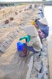 Vietnamesische Frauensalzarbeitskräfte sind entspannend, nachdem sie schwer, zum des Salzes von den Auszugfeldern zu den Speicher Stockfoto