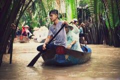Vietnamesische Leute auf tragenden Touristen eines kleinen Holzschiffs lizenzfreies stockfoto