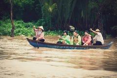 Vietnamesische Leute auf tragenden Touristen eines kleinen Holzschiffs stockfotografie