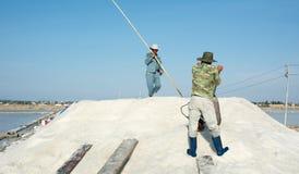 Vietnamesische Leute, die an dem Salzfeld arbeiten Lizenzfreie Stockfotografie