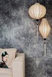Vietnamesische oder chinesische weiße Laternen, spheric und oval, über konkretem Hintergrund des Weinleseschmutzes mit Sofa und v stockfotografie