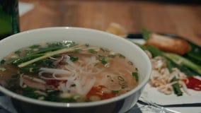 Vietnamesische Suppe Pho BO mit Rindfleisch und Essstäbchen auf männlichen Hand-cousine Asiaten stock footage