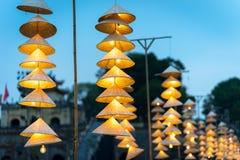 Vietnamesische traditionelle konische Hüte, die am Draht für Dekoration hängen stockbilder