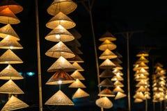 Vietnamesische traditionelle konische Hüte, die am Draht für Dekoration hängen lizenzfreie stockbilder