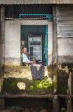Vietnamesischer Mann, der durch ein Fenster, der Mekong-Delta schaut Stockfotografie