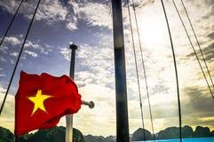 Vietnamesisk flagga på fartyget vid den Halong fjärden - Vietnam Arkivfoto