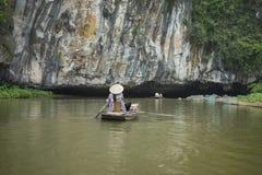 Vietnamesisk kvinna i traditionellt koniskt hattradfartyg in i den naturliga grottan på den Ngo Dong floden, Tam Coc, Ninh Binh,  royaltyfri fotografi