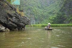 Vietnamesisk kvinna i traditionellt koniskt hattradfartyg in i den naturliga grottan på den Ngo Dong floden, Tam Coc, Ninh Binh,  arkivbild