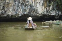 Vietnamesisk kvinna i traditionellt koniskt hattradfartyg in i den naturliga grottan på den Ngo Dong floden, Tam Coc, Ninh Binh,  royaltyfri foto