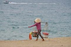 Vietnamesisk kvinna som bär en tung korg Royaltyfria Bilder