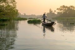 Vietnamesisk kvinna som ror träfartyget på floden Arkivbild
