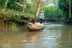 Vietnamesisk kvinna som ror träfartyget på floden Arkivbilder
