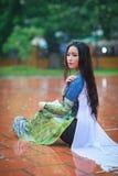 Vietnamesiska kvinnakläder Ao dai i regnet Arkivfoto