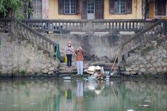 Vietnamesiska kvinnor är be och tvätta kläder på banken av floden, Vietnam Royaltyfria Foton