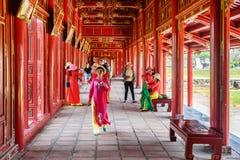 Vietnamesiska kvinnor i färgrika traditionella plagg Ao dai, ton royaltyfria foton