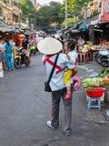Vietnamesiska kvinnor i traditionell konisk hatt med behandla som ett barn på händer s Fotografering för Bildbyråer