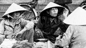Vietnamesiska kvinnor som säljer nya grönsaker på gatan royaltyfri foto