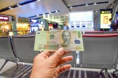 Vietnamesiska sedlar är i händerna av män på flygplatsbakgrunden i Hanoi, Vietnam fotografering för bildbyråer