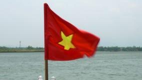 Vietnamesiskt flaggaflyg i vinden på ett fartyg på Thu Bon River, Hoi An, Vietnam stock video