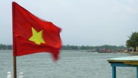 Vietnamesiskt flaggaflyg i vinden på ett fartyg på Thu Bon River, Hoi An, Vietnam arkivfilmer