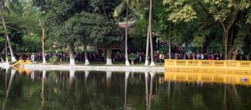Vietnamesiskt folk som matchar i linje för att besöka den Ho Chi Minh Uncle Ho mausoleet Royaltyfri Bild