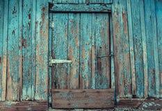 Vieux, abandonné, en bois, peint dans la porte bleue, fendue, putréfiée avec un crochet de la hutte Photographie stock libre de droits