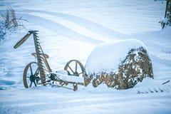Vieux abandonné jusqu'au cultivateur couvert dans la neige à la ferme Photographie stock libre de droits